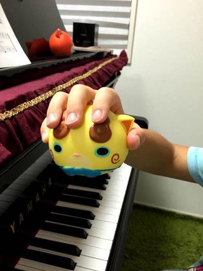 写真 黄色のボールを手の平に握っている