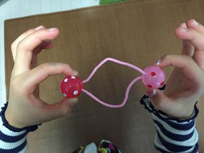 写真 ピンクの髪ゴムを指で握っている